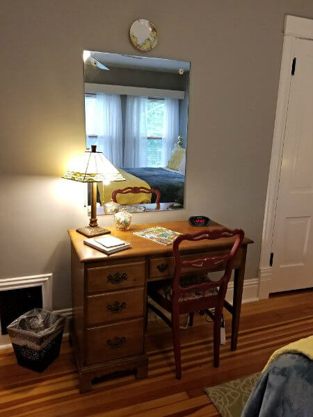 Small wood desk with a mirror and a table lamp with stained glass shade