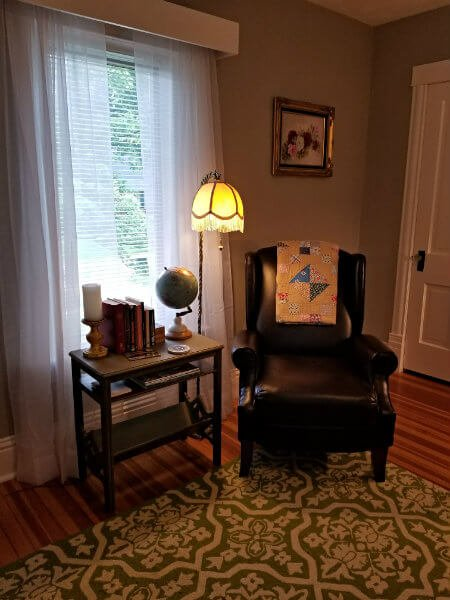 Gray room with wood floor, area rug, dark leather chair, table lamp and side table with books and a globe