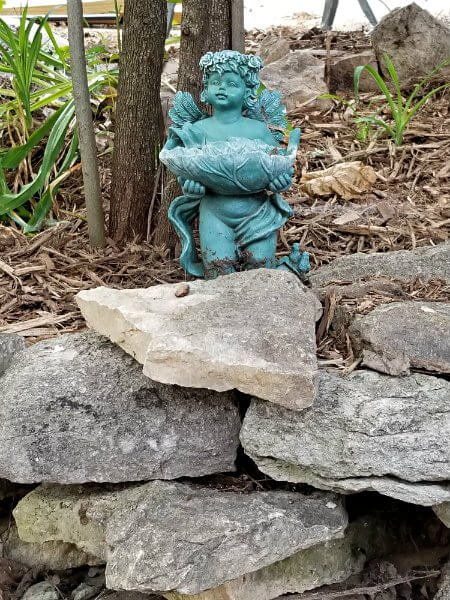 Blue cherub holding a leaf bowl outside among trees, rocks and plants