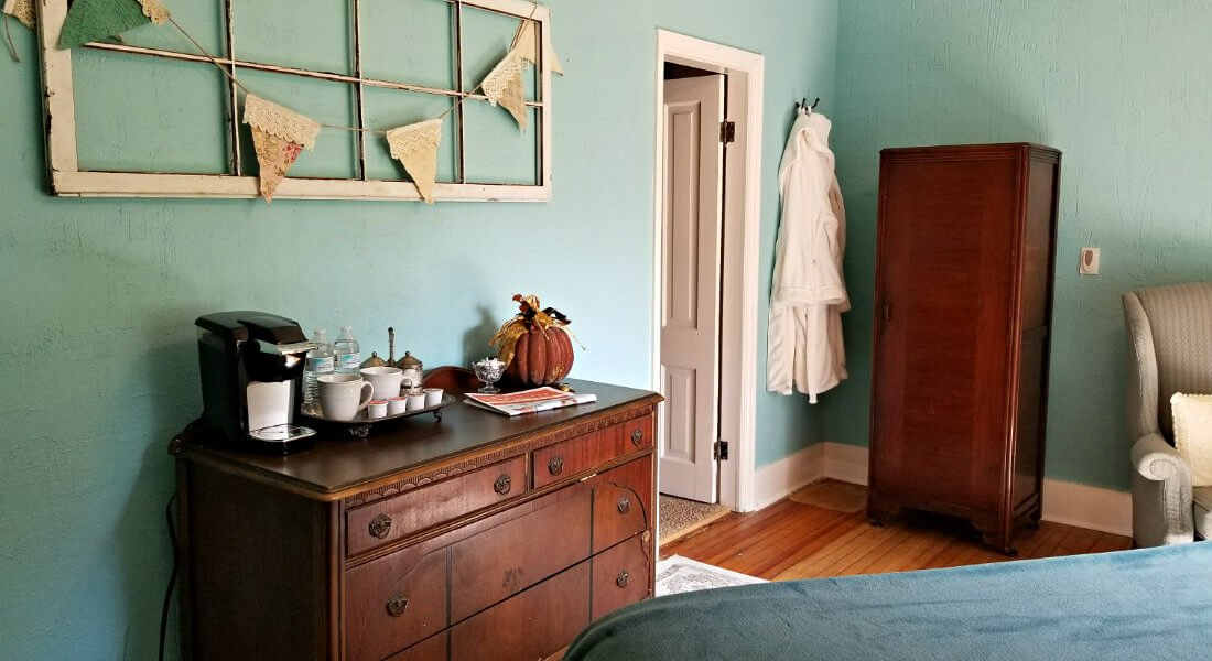 Blue room with white trim, wood floors, wood dresser and hanging white robe