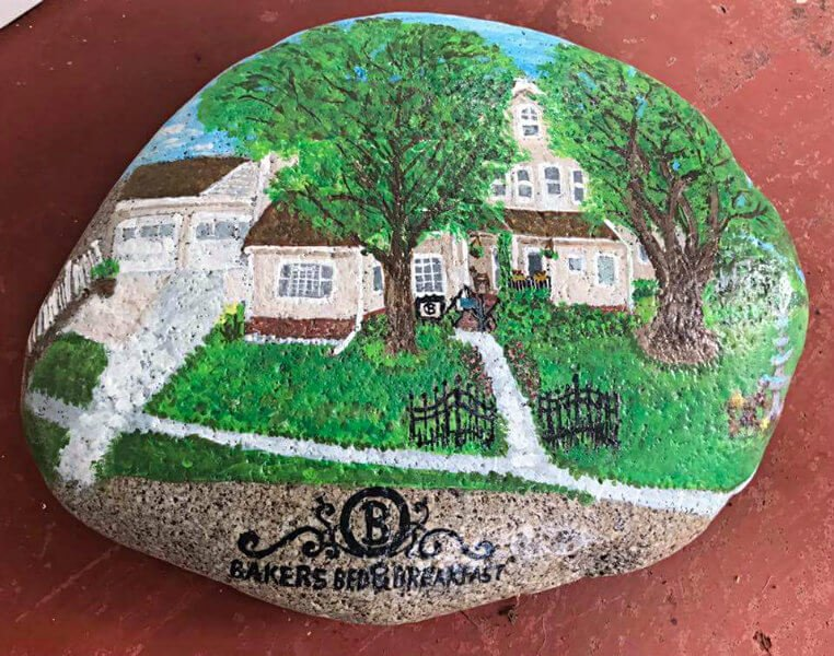 Up close view of a rock with a colorful painting of Bakers Bed and Breakfast