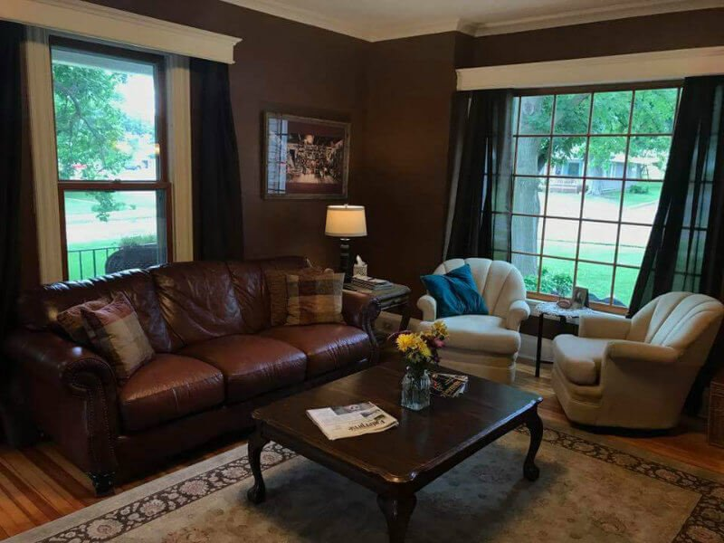 Dark brown room with wood floor, brown leather couch, two beige chairs, a coffee table, and large windows