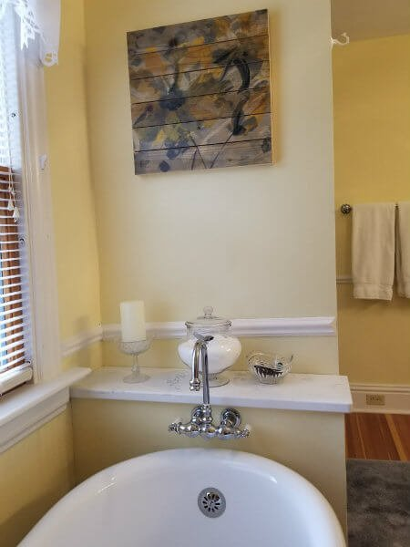 Yellow and white bathroom with wood floor, white claw foot tub , white towels, and a window