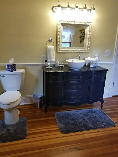 Yellow and white bathroom with wood floor, dark stained ornate vanity with white vessel sink, and blue rugs