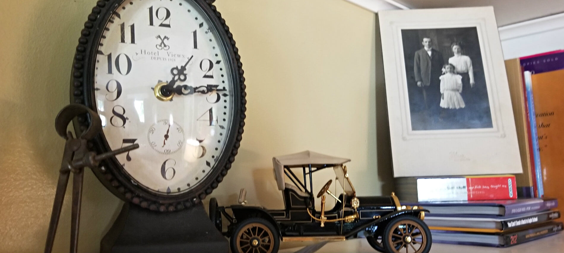 Old fashioned metal clock, old-fashioned model kit car, stack of book and old black and white photo