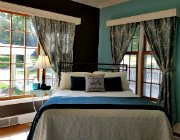 Blue painted room with lots of natural light, blue and white curtains, and metal bed with white and blue bedding