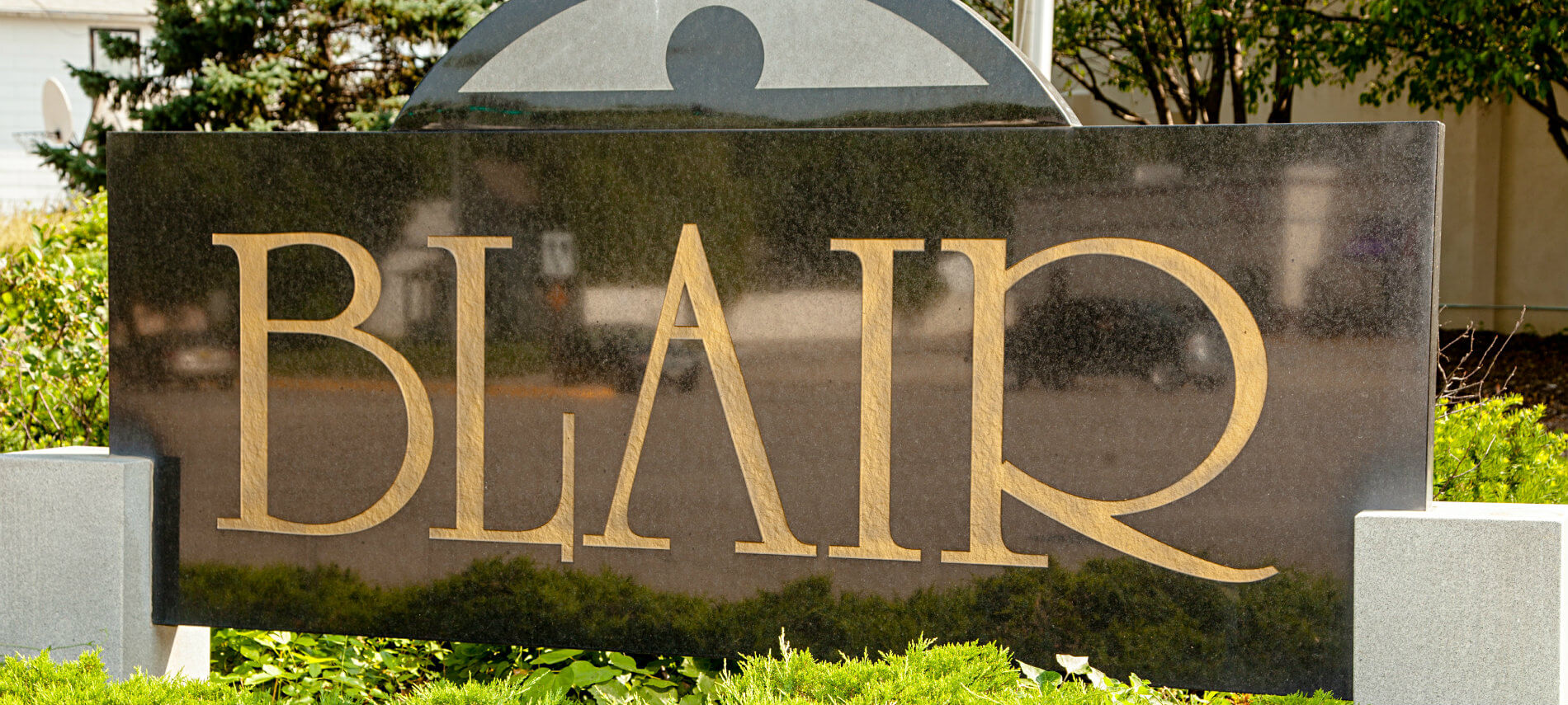 Close-up exterior view of a large, shiny black, stone sign with BLAIR engraved in gold lettering