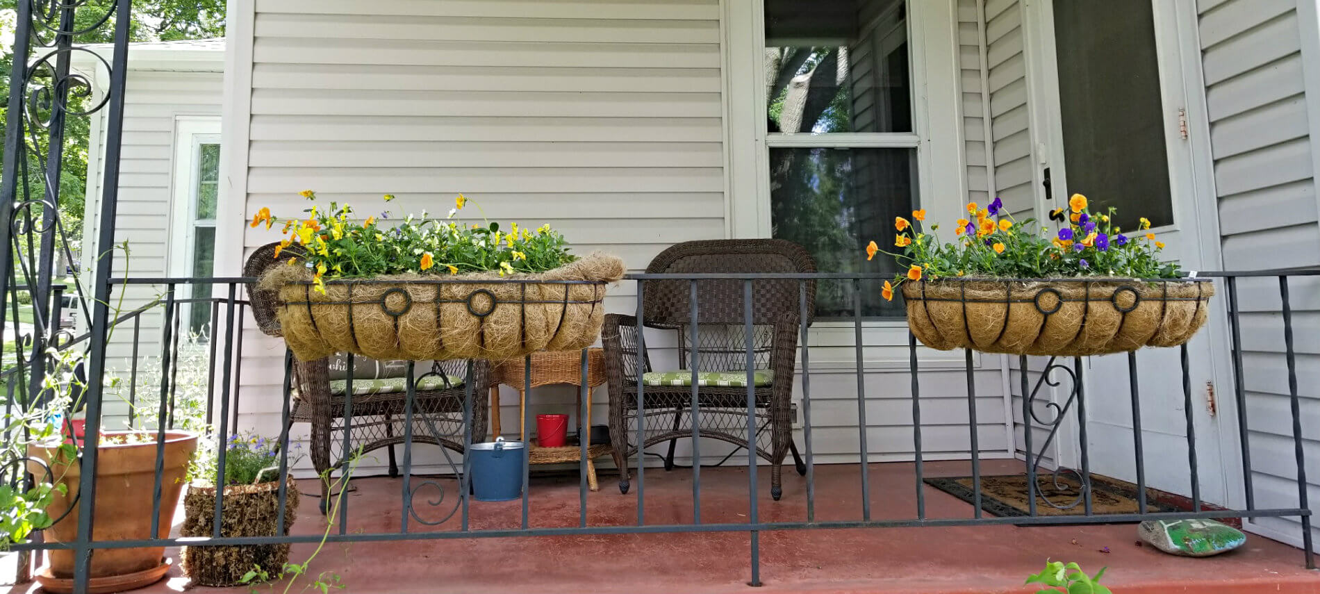Red stained patio with black metal railing, flower pots and baskets, and two wicker chairs with green cushions