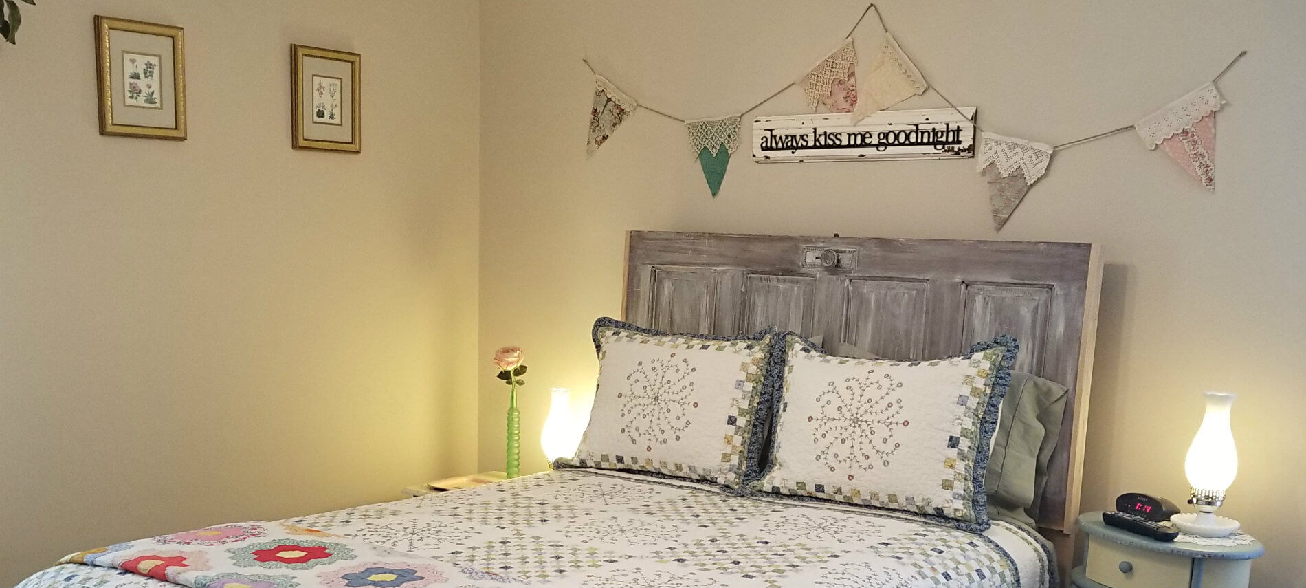 Beige room with quilt covered bed and gray antique door headboard