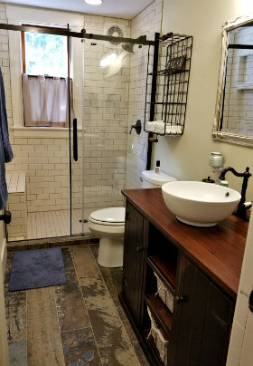 Bathroom with rustic wood floor, tiled walk-in shower with glass door and stained wood vanity with white vessel sink