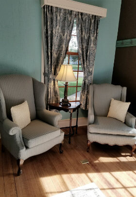 Blue painted room with wood floors and two gray wing back chairs in front of a window