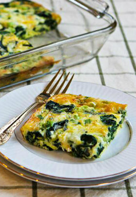 White plate with slice of egg and spinach casserole next to a glass baking dish