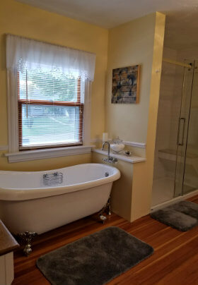 Yellow bathroom, warm wood floors, white pedestal tub, walk-in shower with glass door and white with white lace valance.