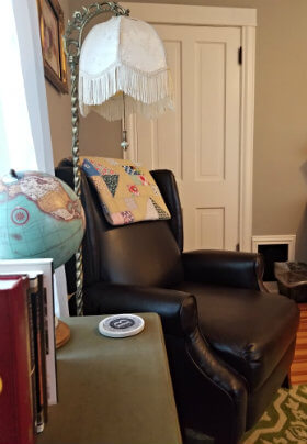 Beige room with dark brown leather chair, arched floor lamp with white fringed shade, side table with books and globe