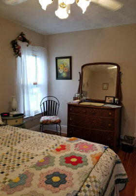 Beige room with quilt-covered bed, window with white sheers, wood dresser with mirror and small ladder back chair